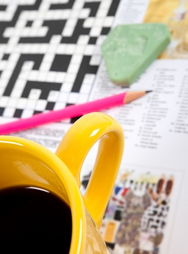 A crossword puzzle with cup of coffee and pencil