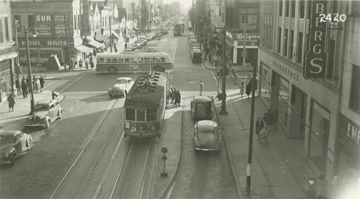 View looking down on a busy intersection with streetcars, cars, and pedestrians.